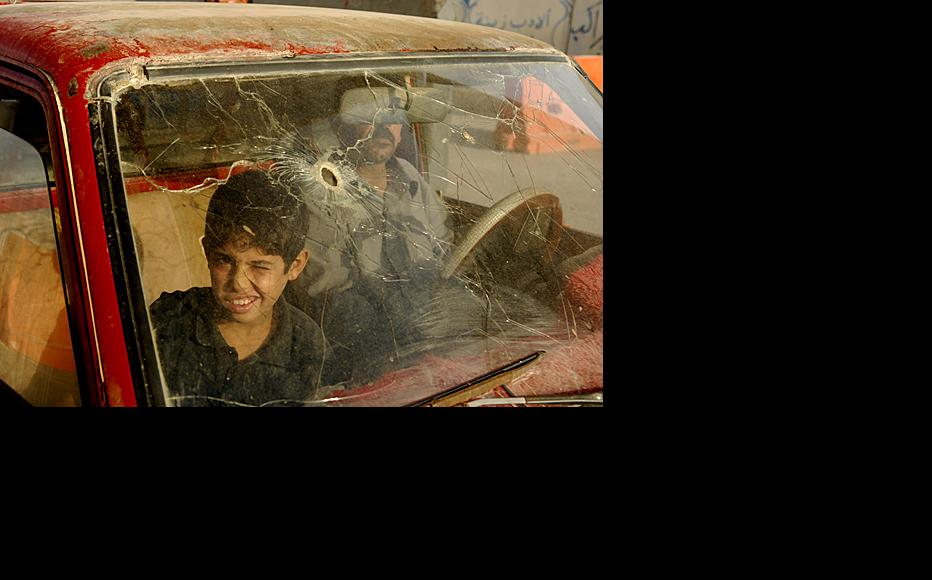 A young boy and his father ride in a car damaged during the fighting. Inhabitants of Fallujah complain that they have yet to be compensated by the authorities for property damaged during the conflict.