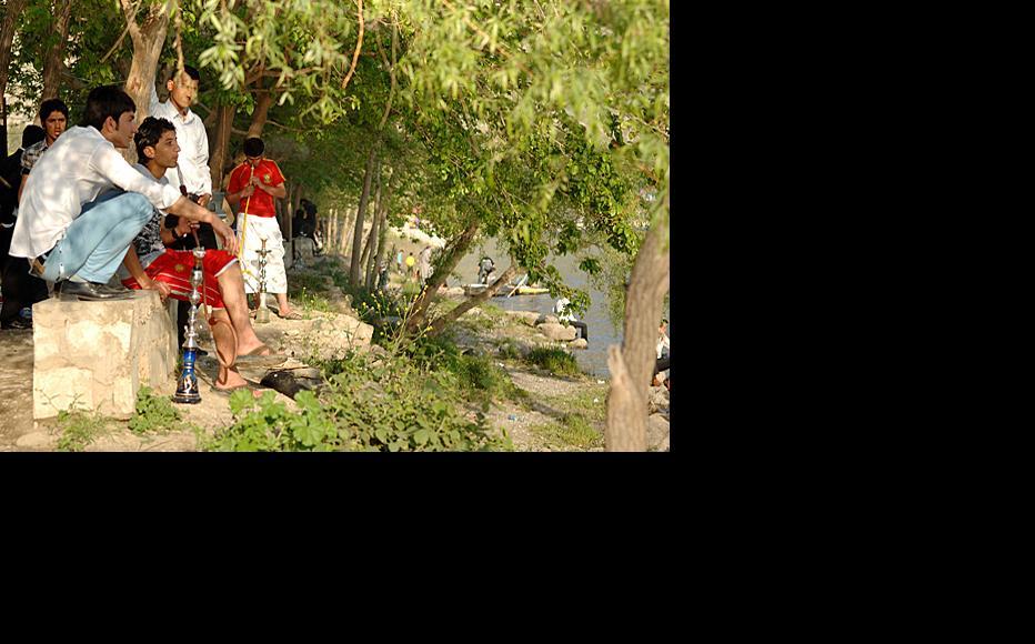 Young men smoke fruit-flavoured tobacco during a picnic at Dukan lake.