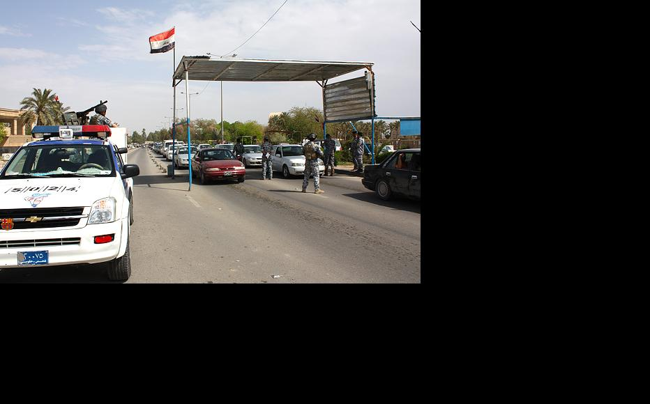 A member of Baghdad operation forces inspects vehicles at a checkpoint near the city's main university in the Jadiriya neighborhood. Iraqi forces established hundreds of checkpoints in 2007 as part of Operation Imposing Law, a joint Iraq-American military effort to restore stability in Baghdad. (Photo by: Emad al-Sharaa)