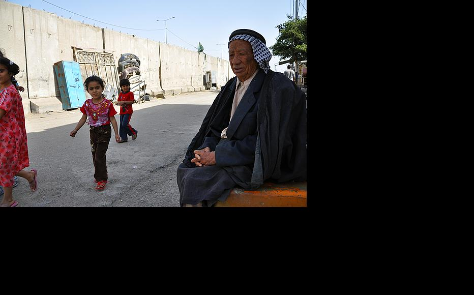 """Shnawa Juma, 70, a resident of the al-Baya neighbourhood in south-west Baghdad, sits in front of his house next to one of the many concrete blast walls that weave around the city. The walls, some of which are now being removed, were erected to limit the movements of insurgents but have been criticised for creating a prison-like environment. """"My house used to be on the main street,"""" he said. """"Now all we can see are the walls."""" (Photo: Haider Khudhr/IWPR)"""