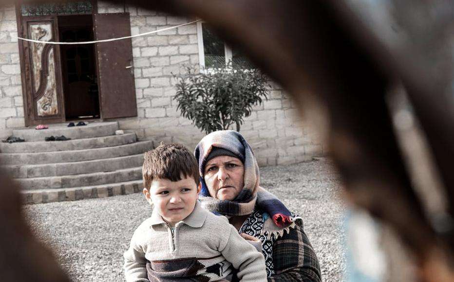 Shahla Gasimova with her young grandson. Artillery fire hit their home, leaving holes in their front door.