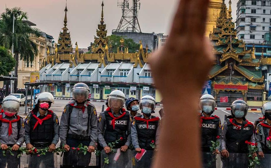 A protester makes a three-finger salute in front of a row of riot police, who are holding roses given to them by protesters, on February 06, 2021 in Yangon, Myanmar.