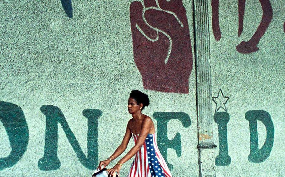 A woman in Havana walks past a sign that reads A Lifetime with Fidel.