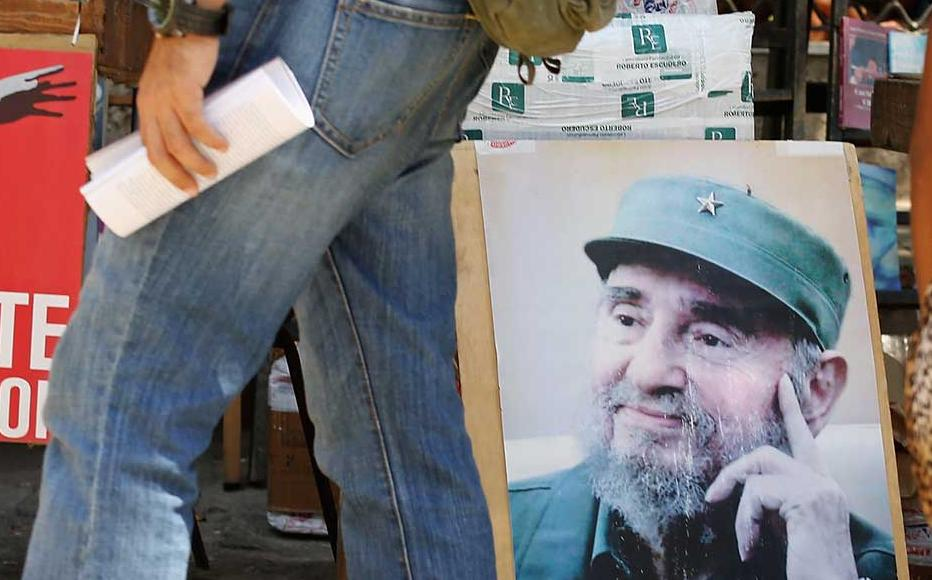 Outdoor booksellers display posters of former Cuban president Fidel Castro in Havana.