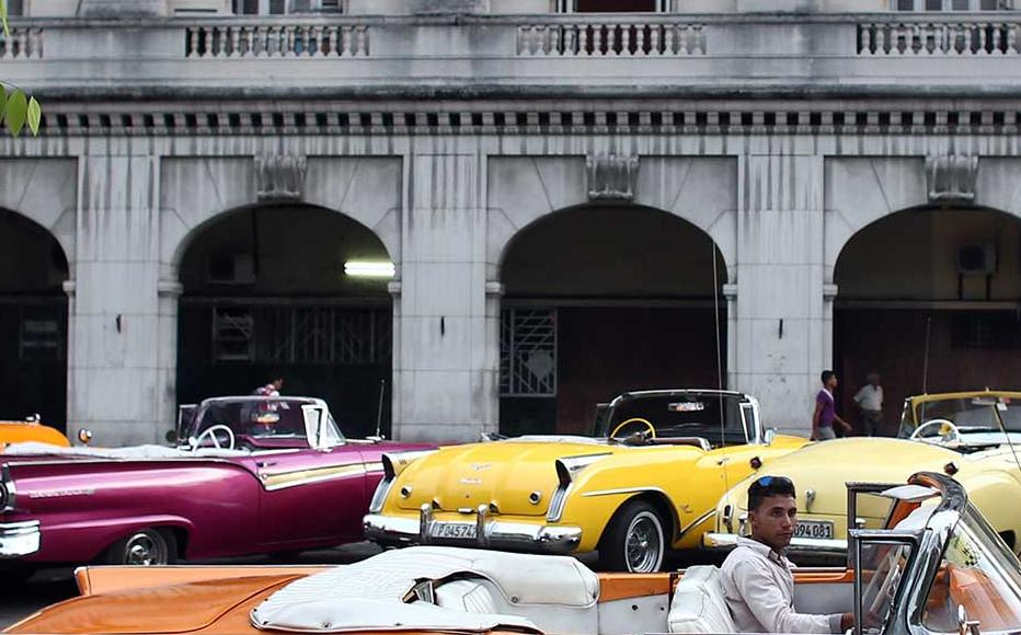 Havana taxi driver sits in a vintage American car.