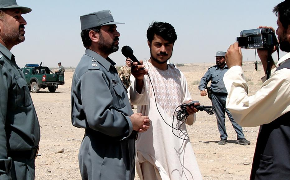Dayee interviewing the head of counter-narcotics in Helmand for an IWPR article in 2007.