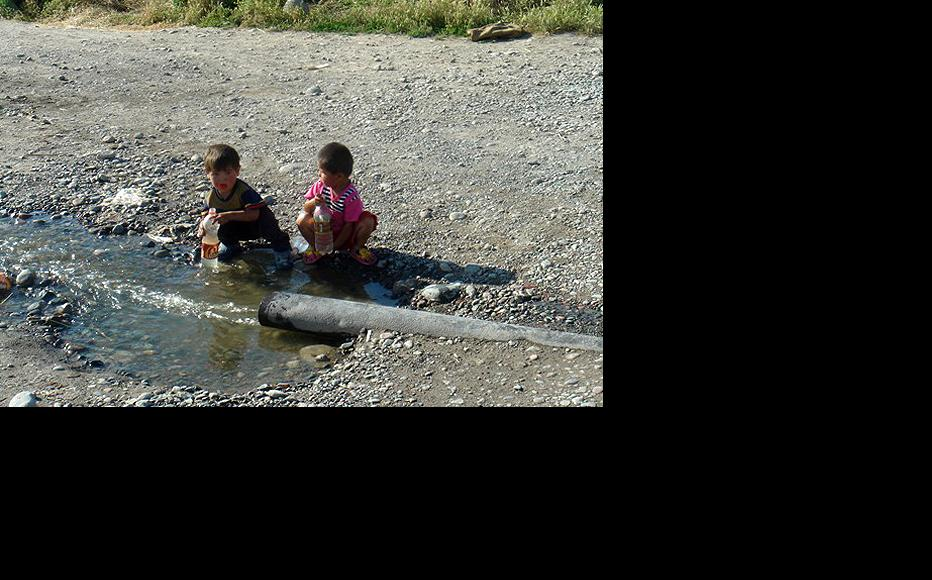 Children drinking water from an open standpipe in Ak Jar. (Photo: Sabina Reingold)