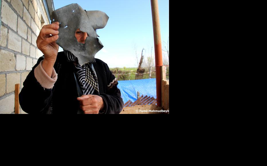 Kifayat Mammadova holds piece of shell which fell on her house in the village of Azad Qaraqoyunlu. (Photo: Famil Mahmudbeyli)