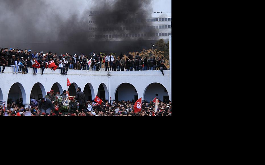 Smoke from burning cars rises as Belaid's coffin arrives at the cemetary, February 8. (Photo: Rabii Kalboussi)