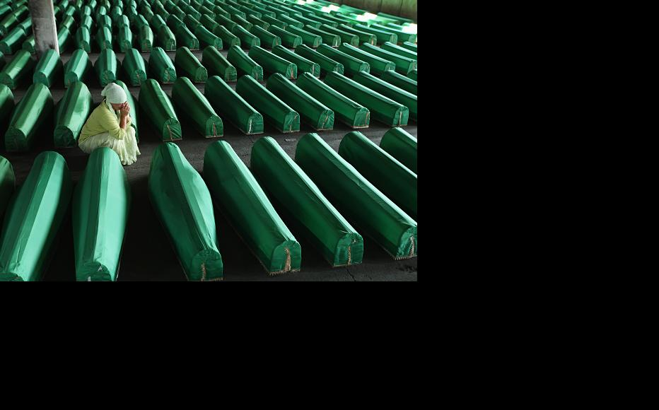 A woman weeps over one of a set of 613 coffins. July 10, 2011. (Photo: Sean Gallup/Getty Images)