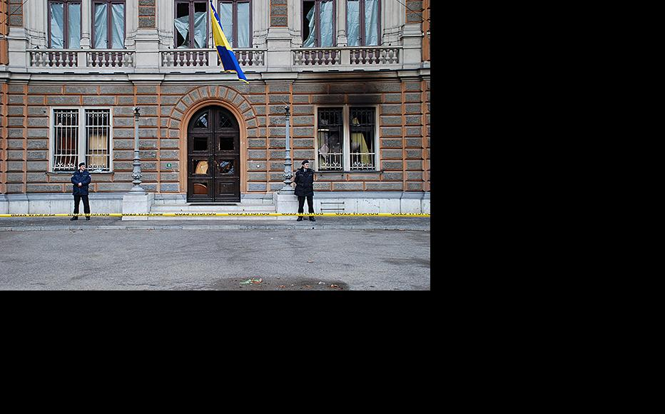 Police guard the entrance to the Bosnia and Herzegovina Presidency, with barricaded doors and fire damage clearly visible. February 9, 2014. (Photo: Jim Marshall)