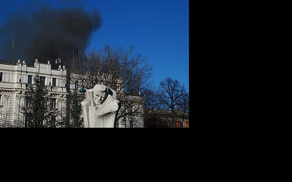Smoke billows from the Sarajevo Canton government behind a statue of Đuro Đaković, a 1920s trade union leader. February 7, 2014. (Photo: Jim Marshall)