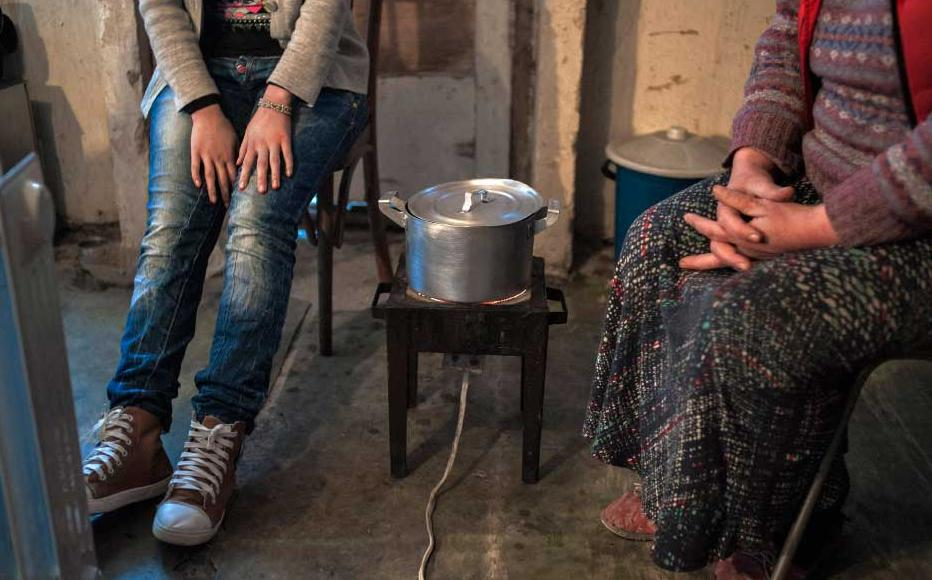 Leyla Tibua (left) and her daughter Sesili wait for dinner to cook on an electric stove.