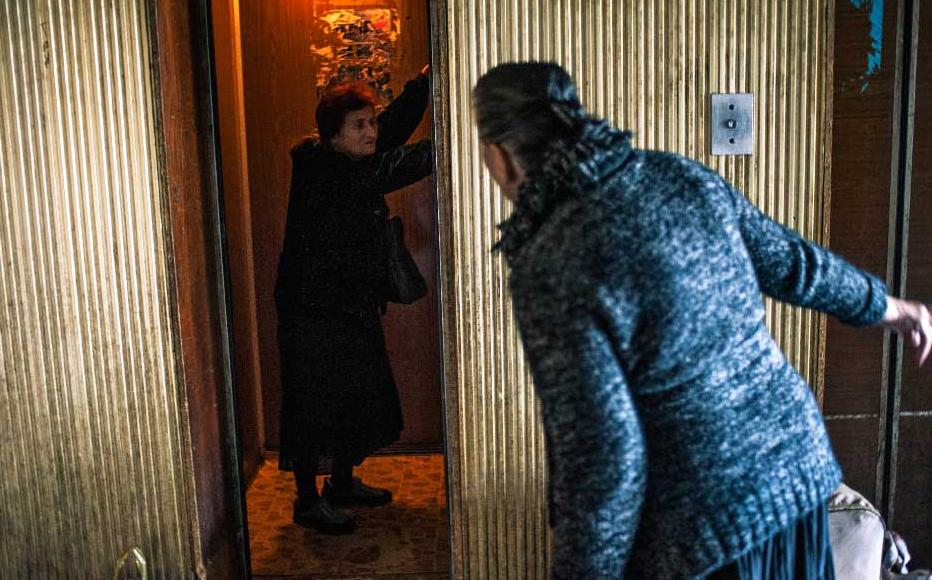 Pensioner Bela Shelia asks a neighbour to wait so that they can use the lift together and save money. Residents pay to use the elevator here.