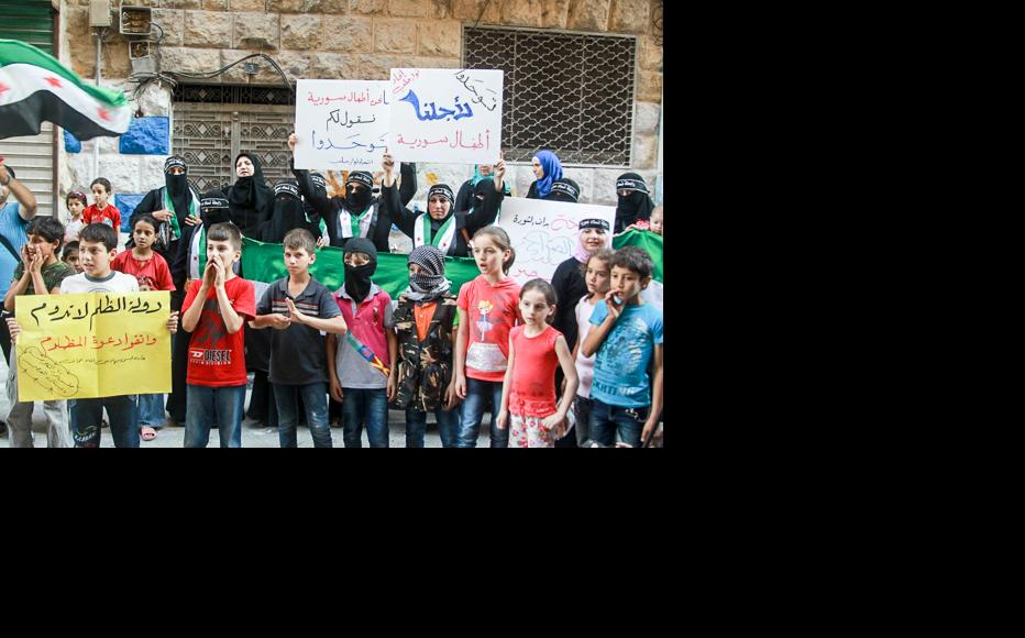"""Members of the Syrian Women's Association call for a united country – """"Stand together for Syria's children."""" (Photo: Ammar Abdullah)"""