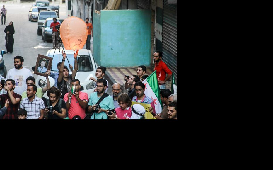 """A balloon with """"Revolution until victory"""" written on it is released. (Photo: Ammar Abdullah)"""