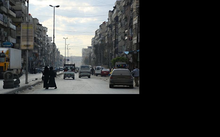 Two women cross a road in Aleppo's al-Fardous neighbourhood. (Photo: Hussam Kuwaifatiyeh)