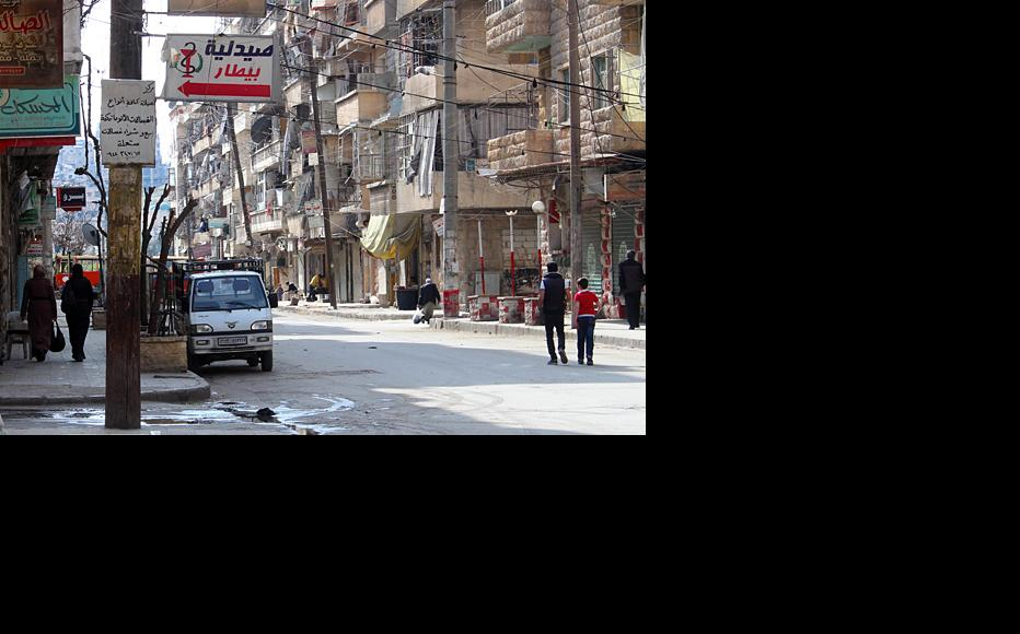 Wreckage of a red public bus down the road separates opposition controlled areas from government-controlled areas in Aleppo. (Photo: Salah al-Ashqar)
