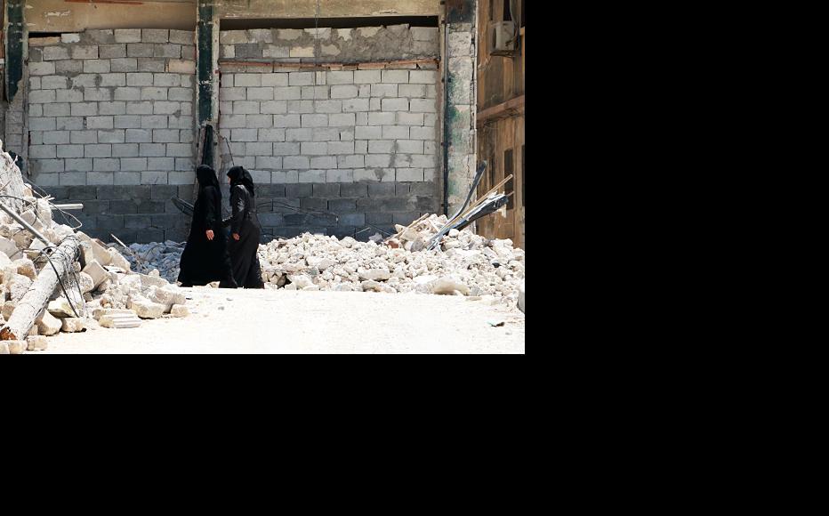 Women walk among the rubble of al-Maadi neighbourhood, Aleppo. (Photo: Baraa al-Halabi)