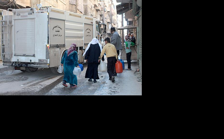 An elderly woman chases after a fire engine to get water as the Amiriya neighbourhood of Aleppo is cut off. (Photo: Damascus Bureau)