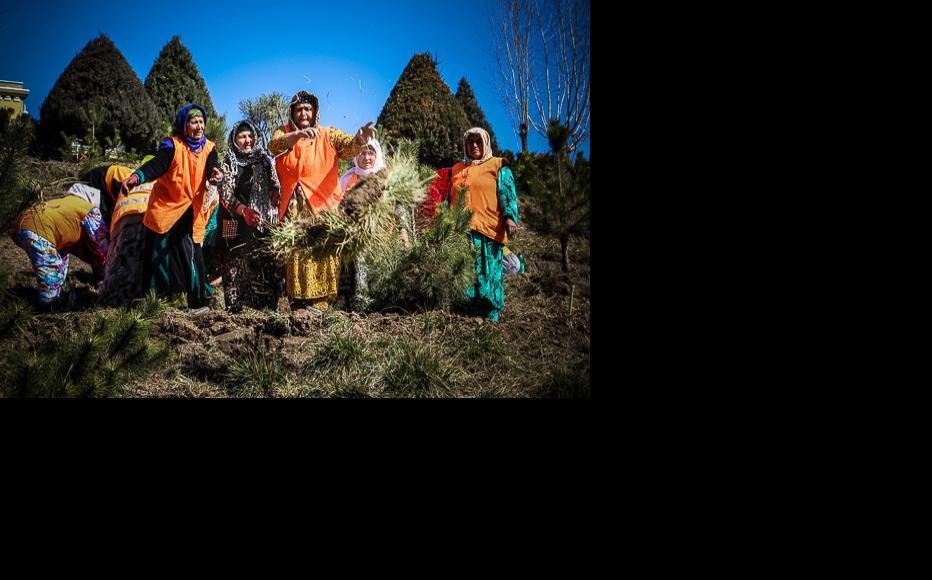 Women wear orange hi-vis vests as they go about their gardening work. (Photo: Lidia Isamova)
