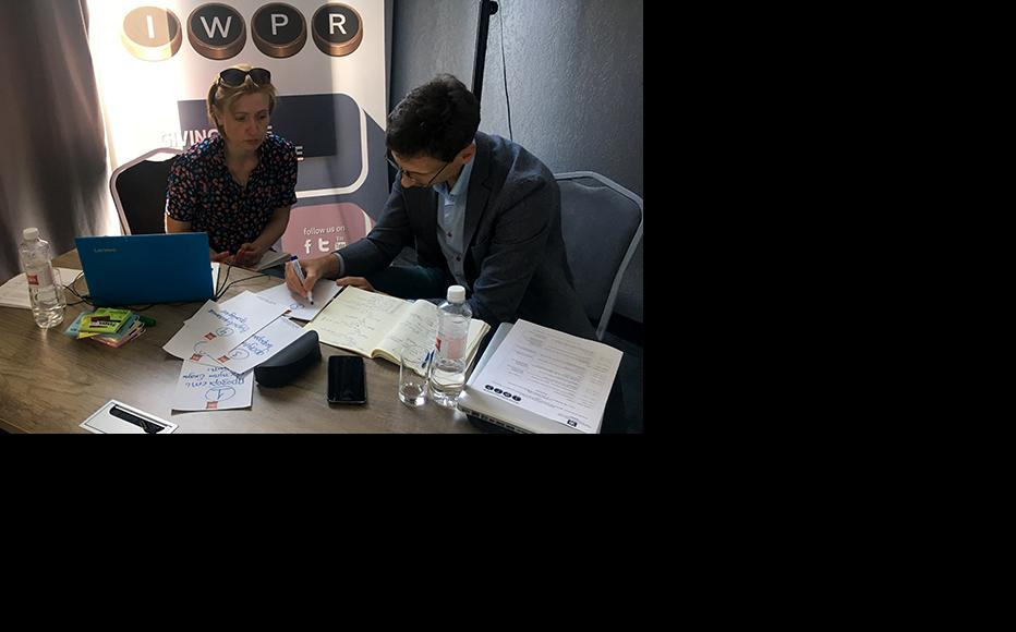 Trainers Iryna Negreyeva and Vitaliy Moroz developing ideas for group work. (Photo: IWPR)