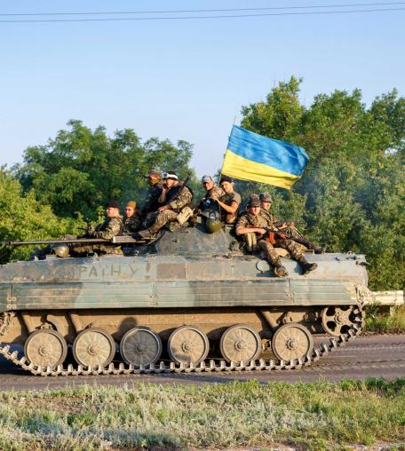 Ukrainian government soldiers sit on top of an armoured vehicle as they take up a position almost 20Km south of Donetsk on on July 9, 2014.
