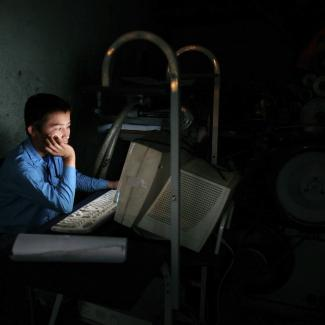 Saif Ali , 15, works on a computer at the Jawid Printing Press shop using a small generator October 31, 2006 in Kabul, Afghanistan.
