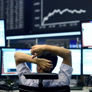 A trader sits at his desk under the day's performance board.