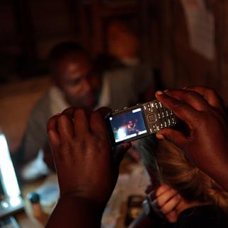 A multimedia interview with a mineral trader in Mubi. While Marie uses her mobile phone as a camera to record material for a video feature, Melanie holds up a microphone for a radio package. (Photo: Tom Bradley)