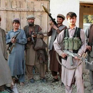 Afghan men display the kind of light weapons that remain prevalent in Afghanistan despite efforts to disband paramilitary groups. (Photo: Davric/Creative Commons)