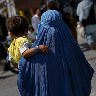 An Afghan woman carries a child in downtown Herat, Afghanistan. (Photo: Chris Hondros/Getty Images)