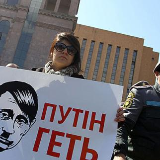 "A protest holds a banner saying ""Putin Get Out"" during a demonstration outside the Russian embassy in Yerevan, March 5. (Photo: Photolure agency)"