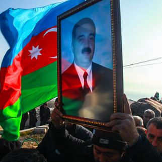 A picture of the late Zaur Hasanov is held up during his funeral. (Photo: Aziz Karimli)