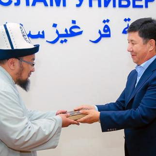 Former prime minister Temir Sariev, gives his old valuable Quran to the lecturer of Islamic university of Kyrgyzstan Chubak Jalilov. (Photo: 24.kg news agency)