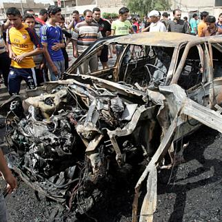 Residents of the sprawling Baghdad slum of Sadr City examine the burned out remains of a car on April 23, hours after the vehicle was used by insurgents to attack a nearby Shia mosque. (Photo: Serwan Azez/Metrography)
