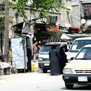 Two women standing in front of a taxi in the Firdaws neighbourhood of Aleppo. (Photo: Hussam Kuwaifatiyah)