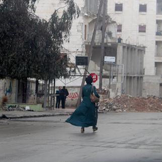 A woman walks along a rubble-strewn street. (Photo: Salah al-Ashqar)