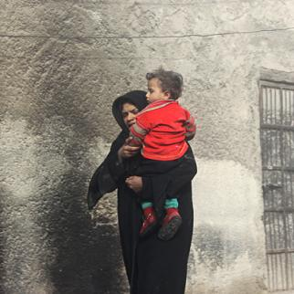 A woman carries her child out of their house that was struck by a shell in the Marja neighbourhood of Aleppo. (Photo: Salah al-Ashqar)