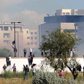Protestors on the embassy walls. (Photo: Jadal News/jadal.tn)