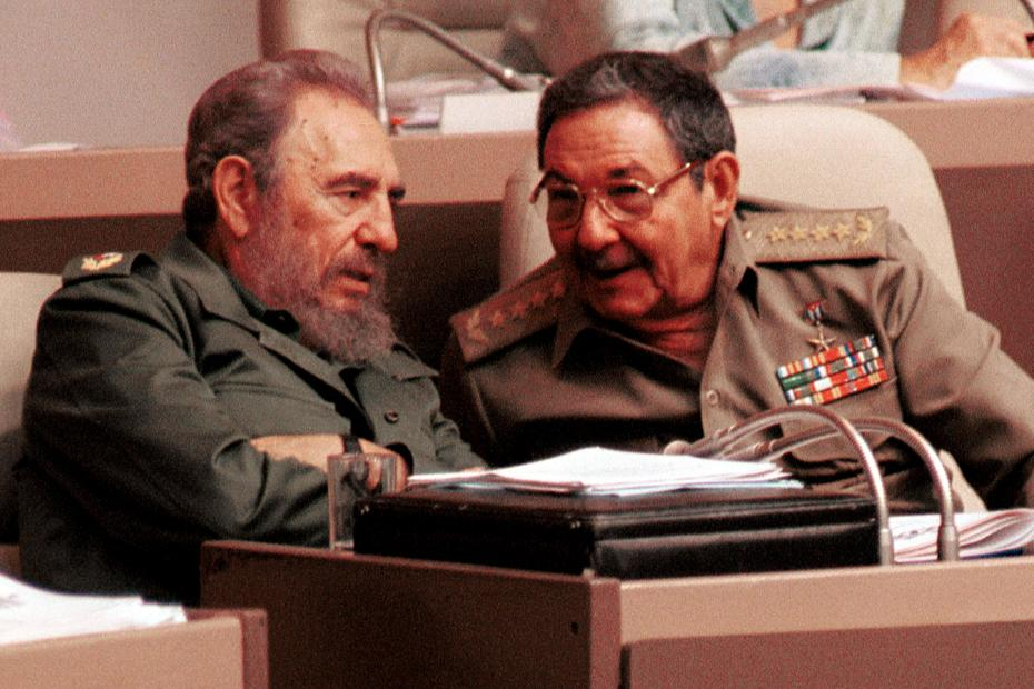 Cuban President Fidel Castro (L) talks to his brother Raul Castro (R) during the Cuban Parliament's session in the Palacio of the Conventions December 23, 2004 in Havana, Cuba.
