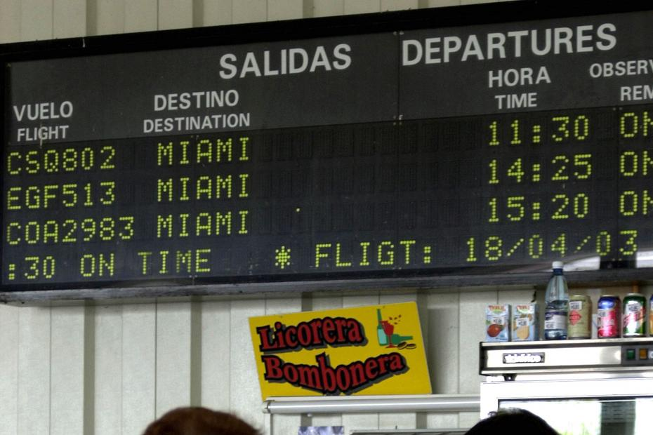 People pass under a departures board at the International airport in Havana, Cuba.